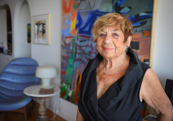 Annie Solomon, wife of the late artist Syd Solomon, photographed in front of one of his paintings in her Sarasota condominium in 2016.