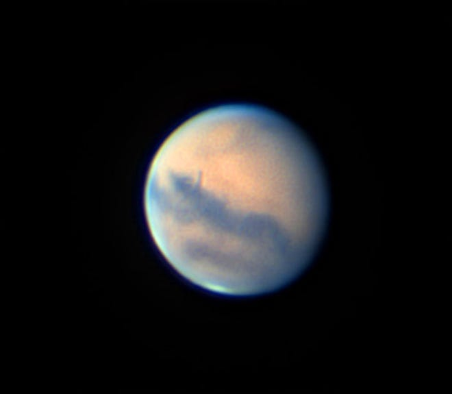 The planet Mars is shown in a photo made Sept. 14 through the author's 14-inch telescope. Dark surface features stand out against reddish Martian deserts, and the south polar cap is visible at the bottom. Bluish clouds and haze cover the north pole at the top. The red planet will make a close pass by Earth on Oct. 6. [Johnny Horne for The Fayetteville Observer]