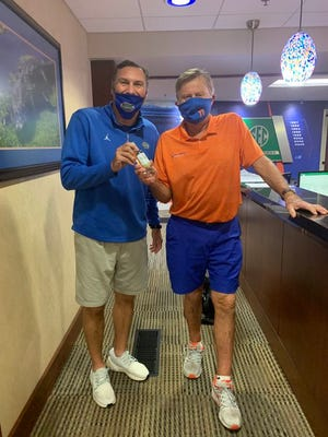 Florida coach Dan Mullen, left, holds a gift from former UF coach Steve Spurrier on Monday.