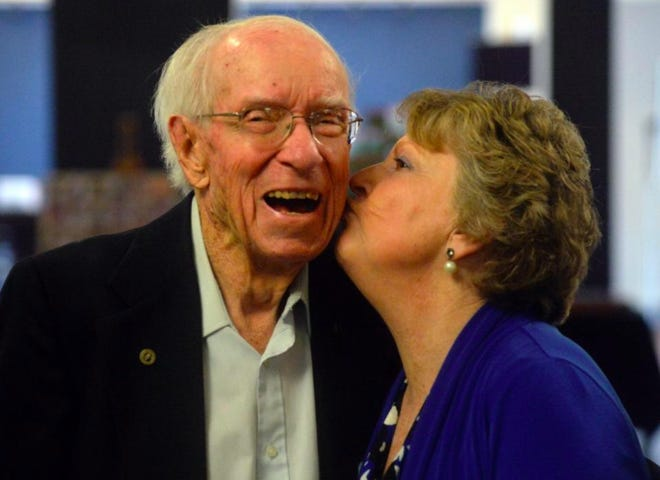 Dr. Charles Kernodle Jr. is given a kiss by Carol Story, the wife of former Williams High School football coach Sam Story, at his 100th birthday celebration in 2017.