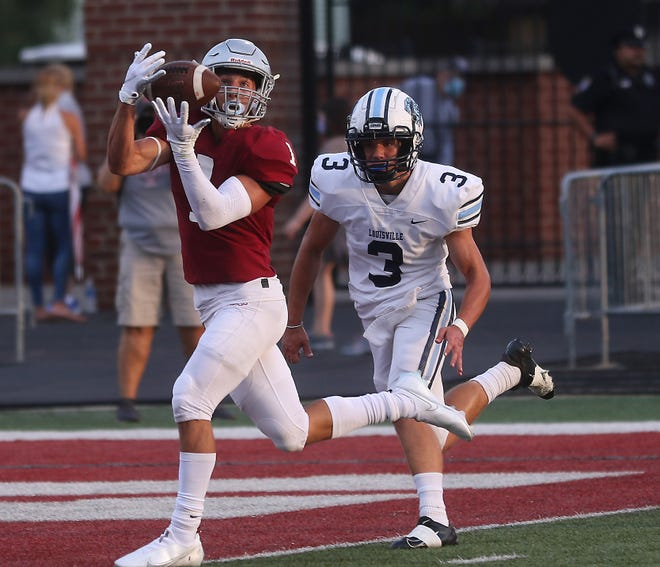 Dover's Nathan Ravine makes a catch at the end zone past a Louisville defender for a touchdown in the first quarter of the home opener at Crater Stadium. (TimesReporter.com / Jim Cummings)