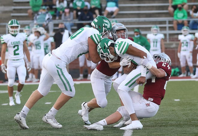 Dover's Doug Weaver (right) helps sack South Fayette quarterback Naman Alemada in their contest at Crater Stadium. (TimesReporter.com / Jim Cummings)