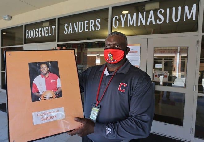 Central High has renamed its gymnasium in honor of legendary coach Roosevelt Sanders. Coach Dennis Connor holds a portrait of Coach Sanders outside the newly named gymnasium Monday Sept. 28, 2020. [Staff Photo/Gary Cosby Jr.]