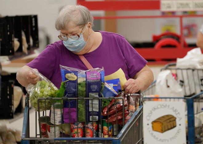 Marie Wirch of Oshkosh selectes food items to take home at the Oshkosh Area Community Pantry on Thursday, Sept. 24, 2020, in Oshkosh, Wis.