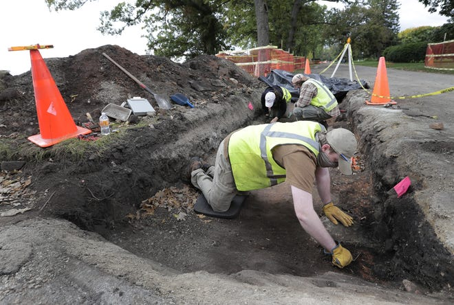 Andrew Behm, an archeological field technician with the University of Wisconsin-Milwaukee Cultural Resource Management program, cleans the floor of a trench to expose the dark stain of a pit that would have been used for cooking. The work is occurring along Lakeshore Avenue in Neenah. Behind Behm is field technician Aimee Jansen, left, and field director Seth Schneider, right.