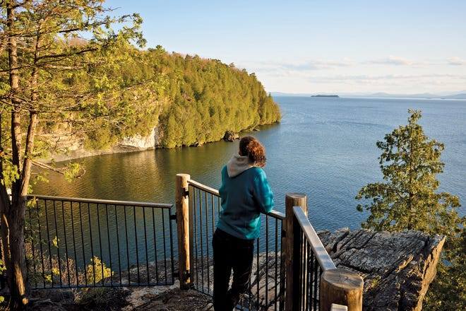 Jenna O'Donnell of Burlington views Eagle Bay (and Juniper Island, beyond), from a newly installed resting spot on a Rock Point trail in Burlington on April 27, 2019.  Conservation and trail upgrades by three contiguous property owners (the Episcopal Diocese, the City of Burlington and Burlington High School) were celebrated Sept. 29, 2020.