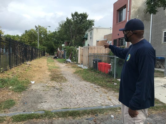 Keith Walker, director of Camden's Department of Public Works, points to an alley the city cleared of trash and debris. However, just a short time later, DPW workers were dismayed to find more trash had been dumped there.