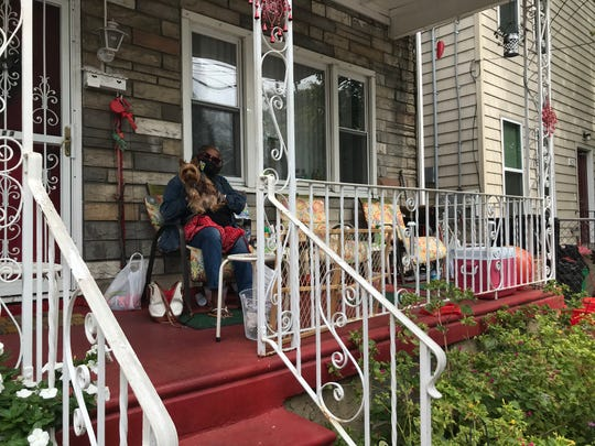Lenora Carpenter and her dog Sarge sit on her porch in the 600 block of Walnut Street in Camden's Bergen Square neighborhood. She and her neighbors say Camden's public works personnel have cleaned trash dumped illegally in some of the lots in the area and hope the work continues.
