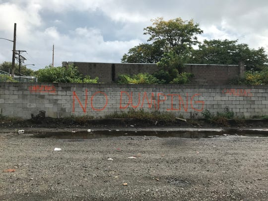Spray-painted warnings that cameras will catch illegal dumpers in the act have been put on a wall on Ancona Street next to Liney Ditch Park in Camden.