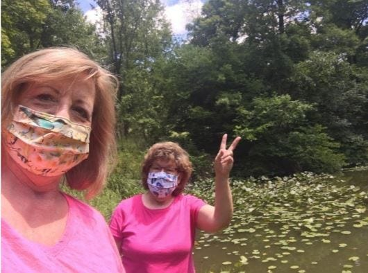 Two masked birders Sherry left and Peggy aid the Ottawa National Wildlife Refuge.