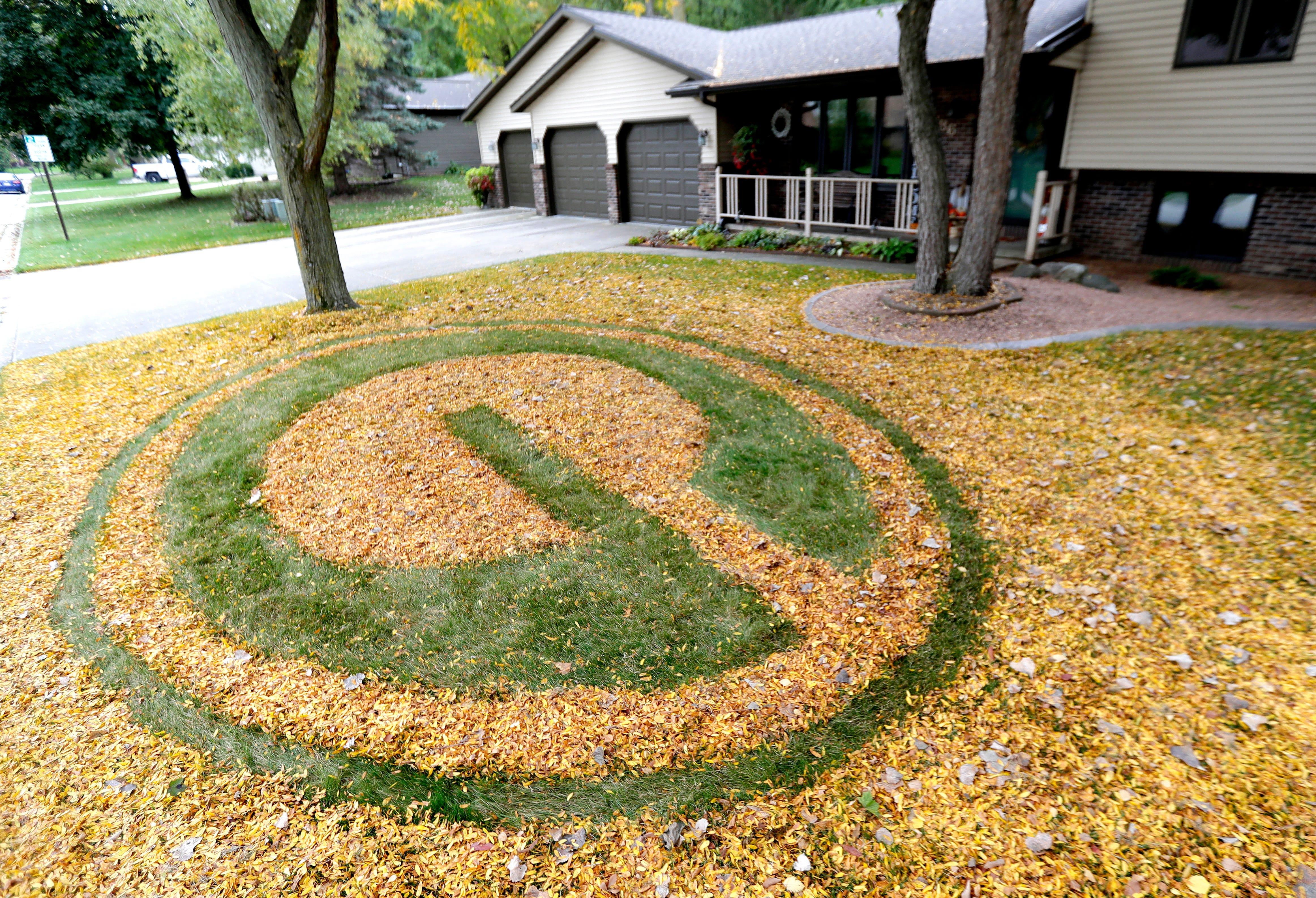Green Bay Packers fan rakes yard into green-and-gold art display