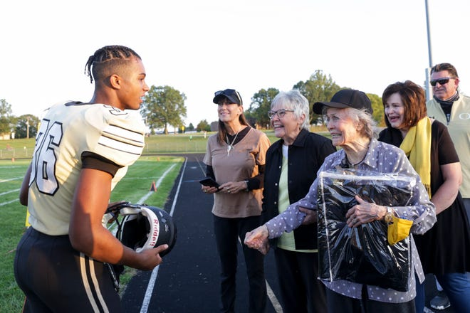 Marilyn Berto reacts as Delphi players greet her before their football game against Clinton Prairie, Friday, Sept. 25, 2020 in Delphi. Berto's late husband, Tony Berto, served as the high school's football coach for over 30 years.