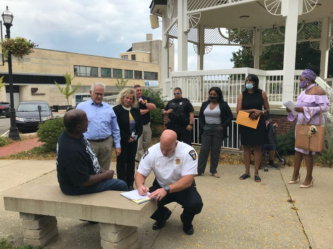 Mansfield police Chief Keith Porch Monday signs his name to the 'Code of Conduct,' an aspirational document outlining expectations for behavior and accountability in the community.
