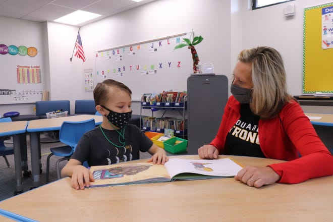 Gus Frank and his kindergarten teacher, Jenny Lindee, read a book at Swallow School in Hartland.