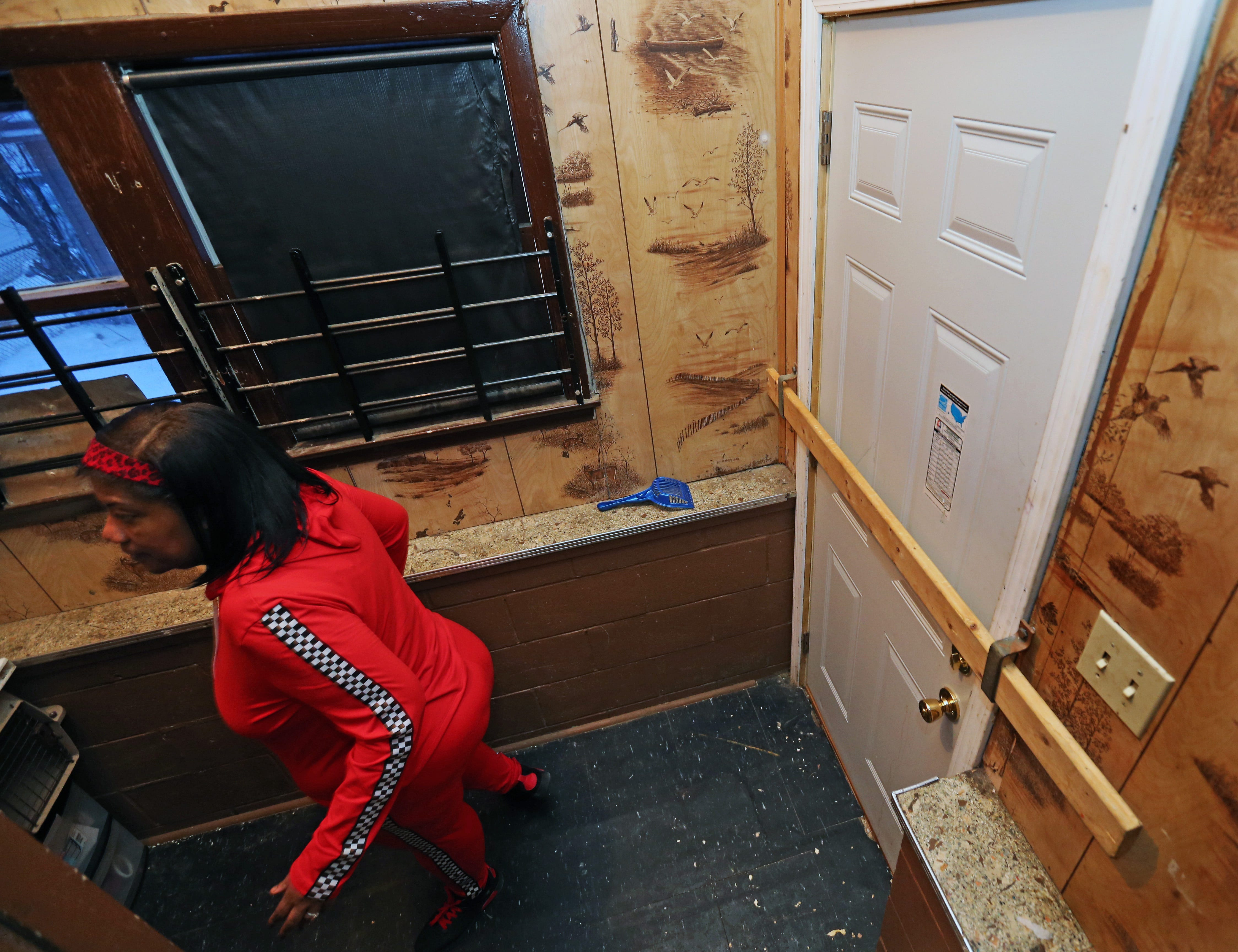 Christy Conery makes her way to her basement, passing by a side exterior door where landlord Lynda Williams uses a board to secure the door, on Jan. 30, 2020, in the 4600 block of North 36th Street. Shortly after moving into the rental property, Conery complained to the city building inspector about such problems as peeling paint, holes in the floor, metal safety bars, and plumbing.  Conery believes those complaints were the reason Williams sent her an eviction notice. Williams said Conery violated a no-pet policy.