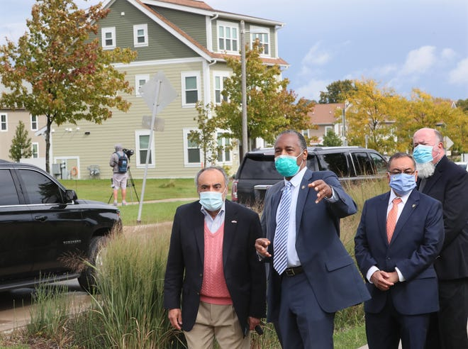HUD Secretary Ben Carson, center, asks questions of Milwaukee Housing Authority Executive Director Antonio Perez while looking at the homes in Westlawn Gardens. Carson visited the Housing Authority's Westlawn property to announce a rule change aimed at steering job and training opportunities to low-income Americans.