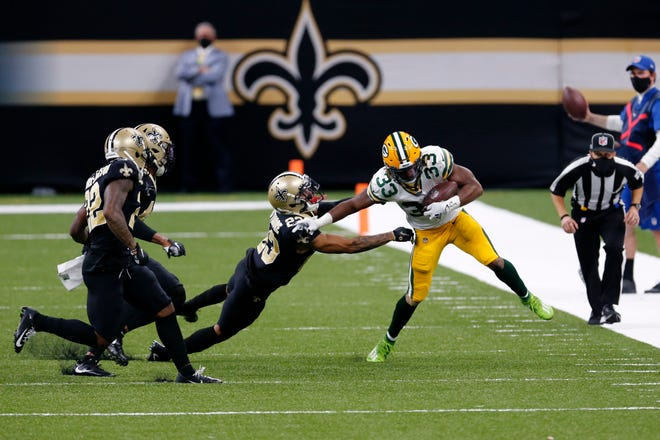 Packers running back Aaron Jones fights off a tackle by Saints cornerback Marshon Lattimore during their game last season.