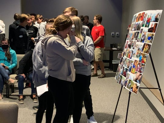 Members of the congregation gather and look at photos of Noah Kimball at a vigil in Brandon on Sunday, Sept. 27, 2020.