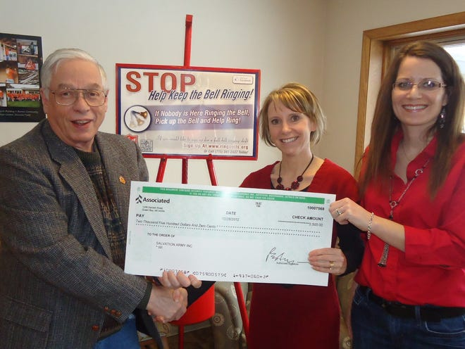 Bob Quam (left) the director of The Salvation Army Hope Center, and Dana Kaminiski, then a case worker at The Salvation Army, accept $2,500 donation in 2013 from Jennifer Fox, vice president and customer care manager of Associated Bank.