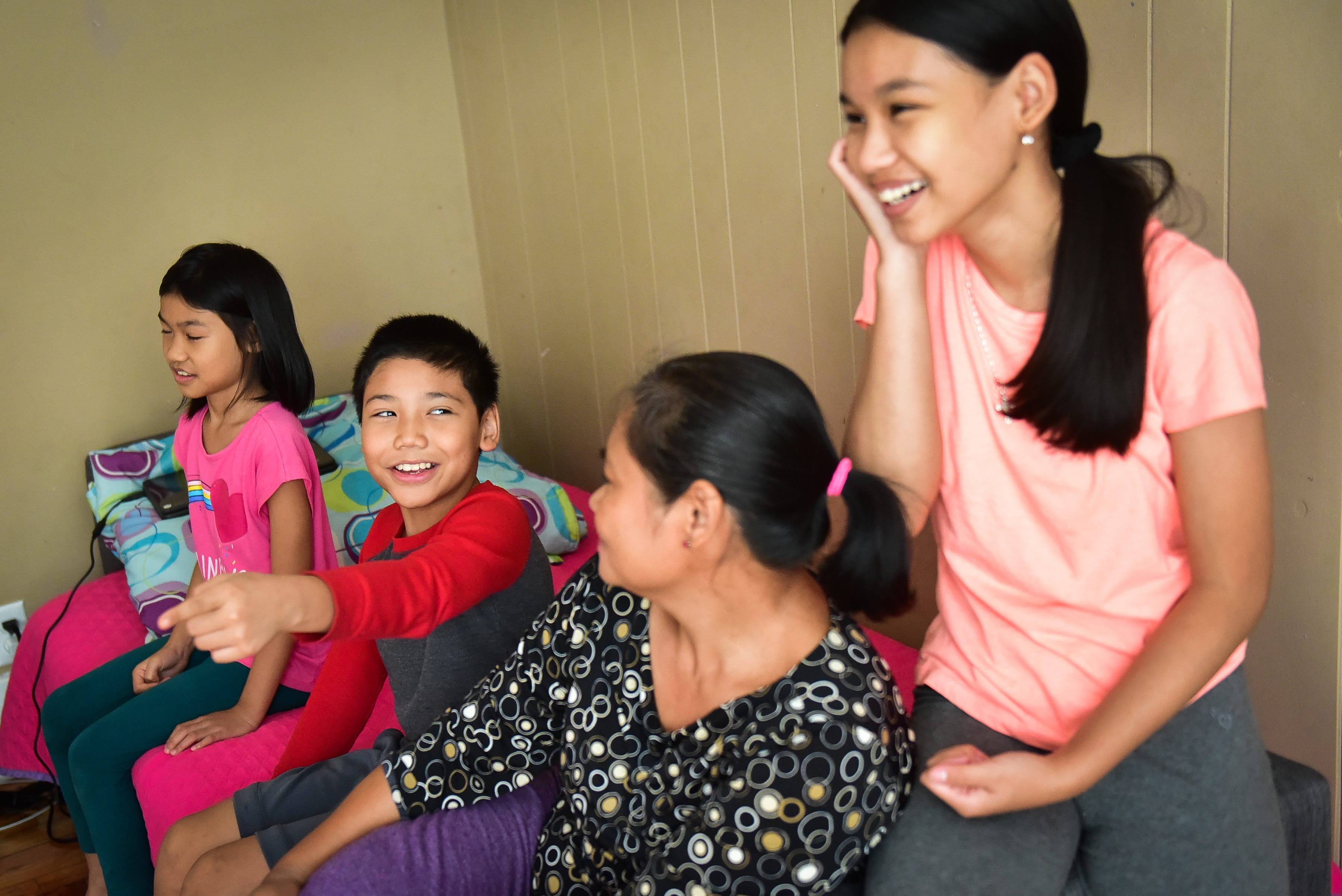 Saw Kler Kaw Htoo, left center, points to one of his sisters and laughs while talking about what it's like to attend classes from home on Thursday, Sept. 24, 2020, in Utica.