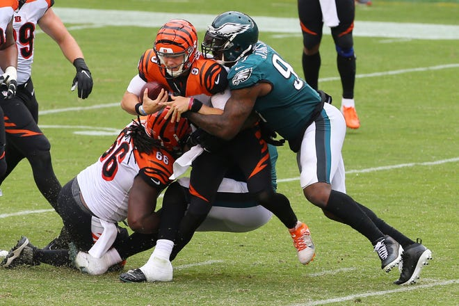 Bengals quarterback Joe Burrow (9) is sacked by the Eagles' Derek Barnett and Malik Jackson, right, during the second half  Sunday in Philadelphia. The game ended after overtime tied at 23.