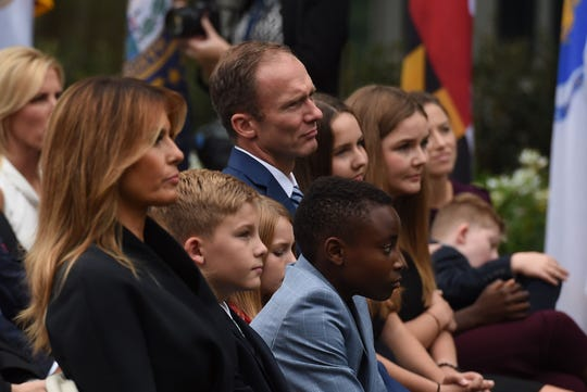 US First Lady Melania Trump (L) sits with Jesse Barret (2nd L), husband of US Supreme Court nominee Amy Coney Barrett and their children, in the Rose Garden of the White House in Washington, DC on September 26, 2020. (Photo by Olivier DOULIERY / AFP) (Photo by OLIVIER DOULIERY/AFP via Getty Images) ORG XMIT: 0 ORIG FILE ID: AFP_8QT6ME.jpg