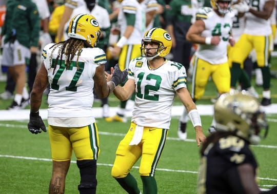 Green Bay Packers quarterback Aaron Rodgers (12) celebrates with guard Billy Turner (77) after a touchdown against the New Orleans Saints during the second quarter at the Mercedes-Benz Superdome.