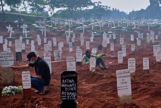 A grave digger takes a break as smoke from fires clearing a new section of cemetery drifts over at a public cemetery, part of which is reserved for suspected COVID-19 victims on Sept. 27, 2020 in Jakarta, Indonesia. Due to a steady rise in COVID-19 cases, Jakarta is running short on hospital beds, quarantine facilities and now graveyard space. There are currently 2 official cemeteries equipped to handle the special protocol for COVID-19 deaths. When asked, nearly all of the men say the saddest part of their jobs is seeing victims arrive with no one to bury them because the family is all in quarantine.