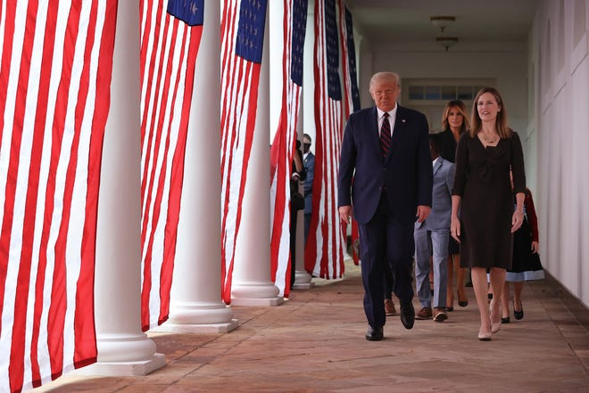 President Donald Trump, first lady Melania Trump, 7th U.S. Circuit Court Judge Amy Coney Barrett, and her family walk along the Rose Garden Colonnade after Trump announced Barrett as his nominee for the Supreme Court at the White House Sept. 26, 2020 in Washington, DC. With 38 days until the election, Trump tapped Barrett to be his third Supreme Court nominee in just four years and to replace the late Associate Justice Ruth Bader Ginsburg, who will be buried at Arlington National Cemetery on Tuesday.