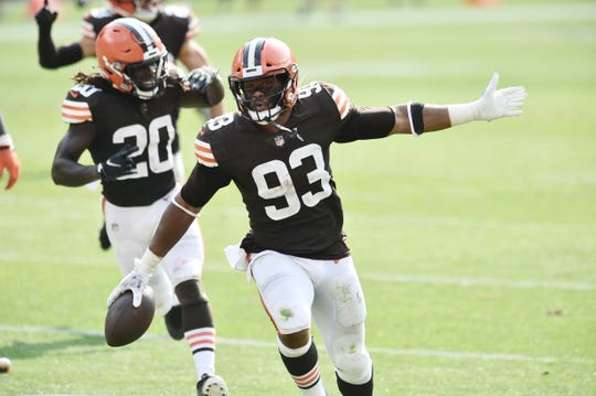 Cleveland Browns middle linebacker B.J. Goodson (93) and cornerback Tavierre Thomas (20) celebrate after Goodson intercepted a pass during the second half against the Washington Football Team at FirstEnergy Stadium.