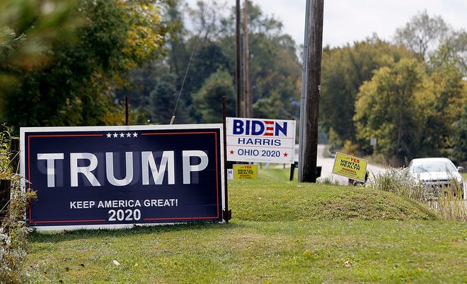 A vehicle traveling north on Ohio 60 in the 2500 block passes by Biden and Trump signs recently.
