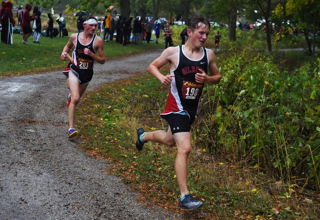 Gilbert's Josiah Schuelka and Sam Vanderpool battle for position as they head around a turn during a rainy varsity boys' race at the Nevada Invitational cross country meet at Hickory Grove Park Monday. Schuelka placed fourth and Vanderpool seventh in helping the Tigers take second as a team.
