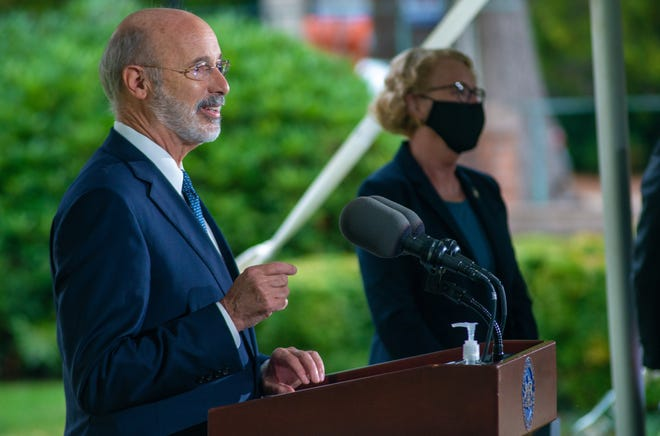 Gov. Tom Wolf makes remarks during a news conference addressing affordable health care Tuesday in Doylestown as state Rep. Wendy Ullman stands in the distance.