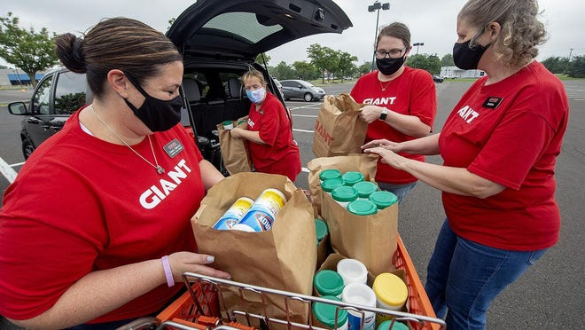 File - From left, Giant store volunteers unload donated canisters of disinfectant wipes for The Help Center in Bristol Borough during the 10th annual United Way of Bucks County Stuff the Bus campaign on Tuesday, Aug. 11, 2020.