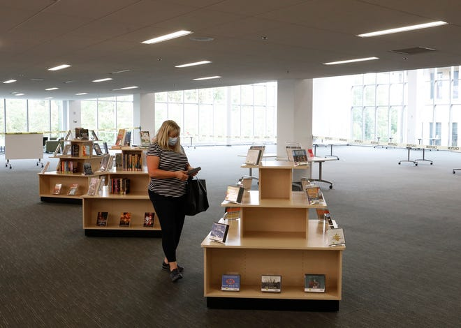 Julie Tufano, of Worthington, looks for audio books at the Columbus Main Library in downtown Columbus on Sept. 29. Tufano was back on the first day they opened and was glad to have the library back for browsing and getting material for her work commute.