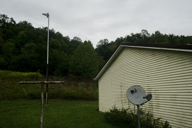 A cell phone booster station, left, sits near Heather Mitchell's home on Monday, August 31, 2020 in Amesville, Ohio. She installed the booster after moving in but still has difficulty getting a reliable cell phone signal, which is her only access to internet. The satellite, at right, isn't hooked up, and satellite internet is prohibitively expensive for Mitchell.