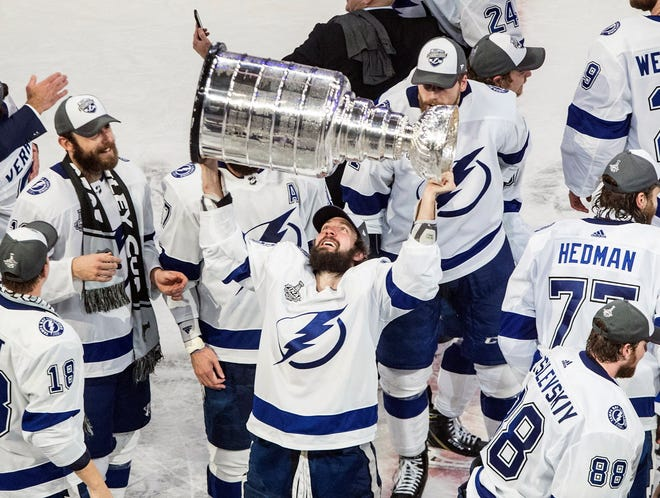 The Lightning's Nikita Kucherov hoists the Stanley Cup after Tampa Bay beat Dallas 2-0 in Game 6 on Monday night in Edmonton, Alberta. [Jason Franson/The Canadian Press]
