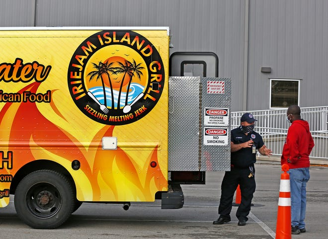 Inspector Kent Wareham, left, talks with Iriejam Island Grill food truck owner Augustine Boamah during an inspection at the City of Columbus Division of Support Services on Tuesday.