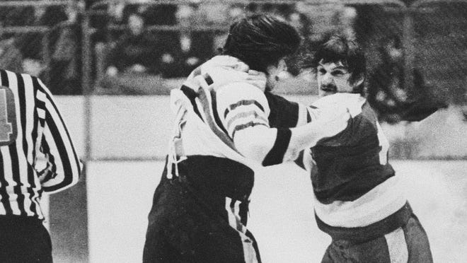 """In a still from the documentary """"International Incidents,"""" Mike Powers of the Columbus Owls, left, tussles with Frank """"Seldom"""" Beaton of the Flint Generals in a game at the Ohio State Fairgrounds Coliseum from the 1973-74 season."""