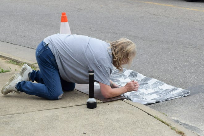 Charlene Milliner, a volunteer at the Humane Society of Guernsey County, checks their live trap as they try to rescue a 6-week-old kitten that is stuck in the drain under East Wheeling Avenue and North 19th Street.