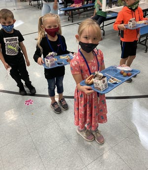 Northwestern Elementary School first-graders hold their lunch trays on Monday. The USDA extended its summer meal program through Dec. 31, meaning all kindergarten through grade 12 students at the district can get free breakfast and lunch.