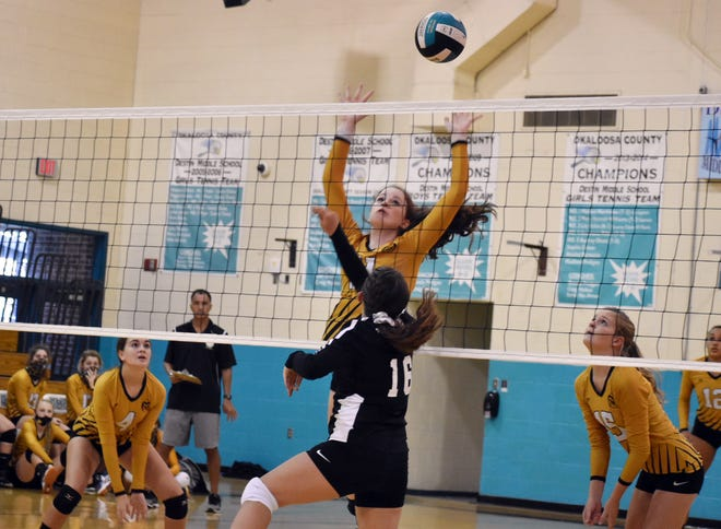 Destin's Brook Henderson tips one over on the Ruckel Rams in middle school volleyball action.