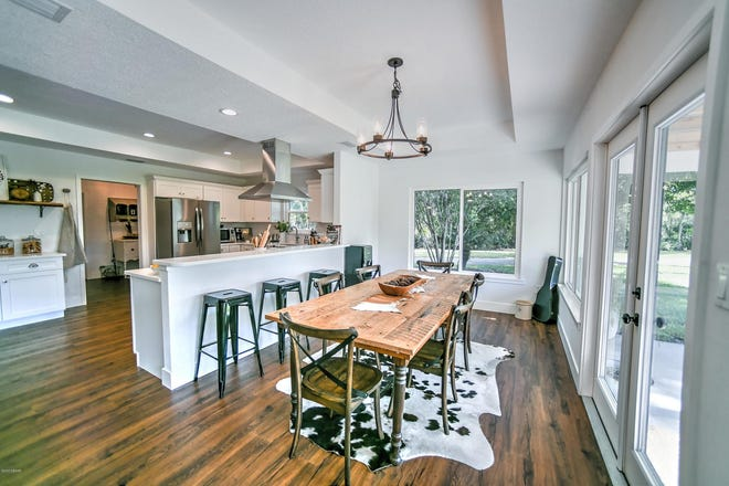 Luxury vinyl-plank, wood-like flooring covers the open-floor plan – from the dining room to the fully remodeled kitchen, with stainless-steel appliances, white cabinets, quartz countertops and a breakfast bar.