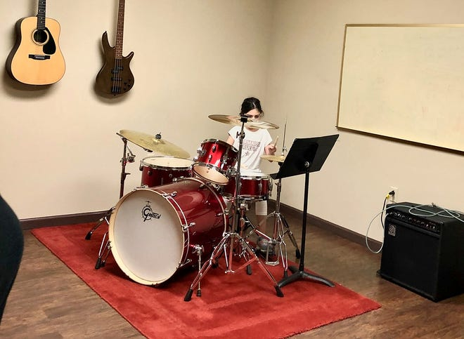 A student practices drums at Rockin' Mozart Music School.