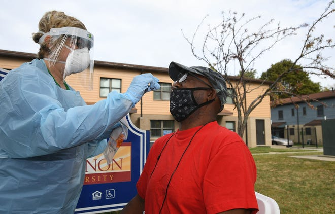 Toni Gomacki, L.P.N., 51, at left, performs a COVID-19 test Tuesday on Curtis Morrow, 60, of Erie, outside the John Horan Apartments on Erie's east side. The free coronavirus tests were provided by Latino Connection, a Harrisburg-based Latino and minority outreach company.