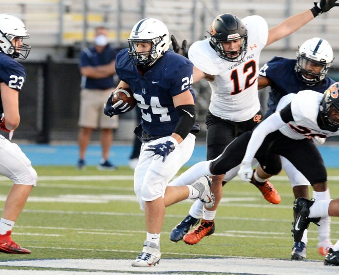 McDowell senior Taha Ramahi, center, runs against Cathedral Prep at Gus Anderson Field on Friday. The Trojans beat Prep 24-10 and moved into the No. 1 spot on District 10 Class 5A-6A.
