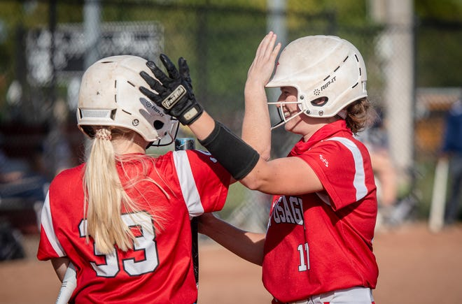 Fort Osage leadoff hitter Kyra McIntosh, right, gets a pat on the head as congratulations from teammate Alysa Garlock after slugging a home run in the third inning of Monday's game against William Chrisman. McIntosh's sixth home run of the year helped the Indians to a 10-5 victory.