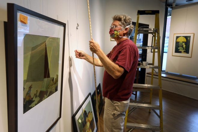 """Fritz Goeckner hangs art for the Art Center of Burlington's upcoming show titled """"Expected and unexpected by John Weyl"""" Tuesday in the downtown Burlington art gallery. The show runs from Oct. 1 to 31."""