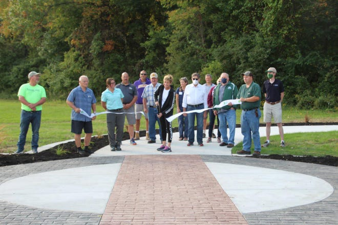 The ribbon cutting at the newly resurfaced Hoover Nature Trail was held Saturday at Chinkapin Bluffs. It was held at the new trailhead, located at the Louisa County Fairgrounds in Columbus Junction. Those taking part in the ribbon cutting were, from left to right, Scott Heater, Ron Durbin, Katie Hammond, Tony Humiston, Jeff Snyder, Mark Huston, Jeannie Mott, Laura Semken, Al Bohling, Shawn Hawks, Karen Minnis, Roger Hunt, Sam Willson and Steve Pedrick.  The group consists of a combination of Louisa County Conservation Board and staff, Fair Board, Trails Council and Tri-Rivers Conservation Foundation directors.