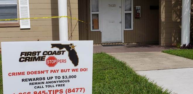 A First Coast Crime Stoppers sign stands in front of the Kona Avenue apartment where a woman was shot early Tuesday, the injury causing her unborn child to die, police said.